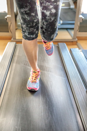 Close up of woman feet in gym shoes running on treadmill machine indoor. Fitness center training. Healthy lifestyle concept.