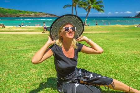 Woman relaxing in Hanauma Bay Nature Preserve, Oahu, Hawaii, USA. Smiling female in black beachwear, floppy hat, sunglasses enjoying on hawaiian beach. 版權商用圖片