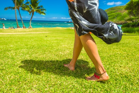 A woman walking barefoot with red anklet on Hanauma Bay Nature Preserve grass, Oahu, Hawaii, United States.