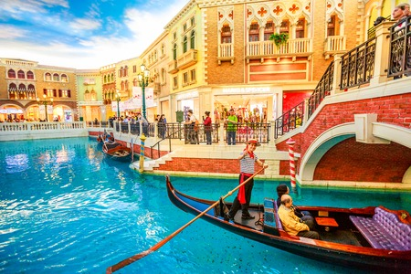 Macau, China - December 9, 2016: gondolier on famous italian gondola with tourists on a romantic ride on the canals of the Venetian Luxury Hotel and Casino and mall. 報道画像