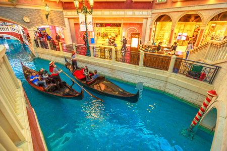Macau, China - December 9, 2016: gondoliers with tourists on a ride by gondola on the Grand Canal of the Venetian Casino. In luxury shopping mall in the Venetian Hotel, Cotai Strip.