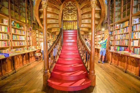 Oporto, Portugal - 13 de agosto de 2017: gran escalera de madera con escalones rojos dentro de la biblioteca Lello e Irmao en el centro histórico de Oporto, famoso por la película de Harry Potter. Disparo horizontal.