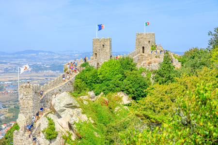 Sintra, Portugal - August 7, 2017: aerial view of ancient wall and tower of Castle of the Moors and Sintra valley. Many people walk over the defensive walls in one of Sintras most popular attractions