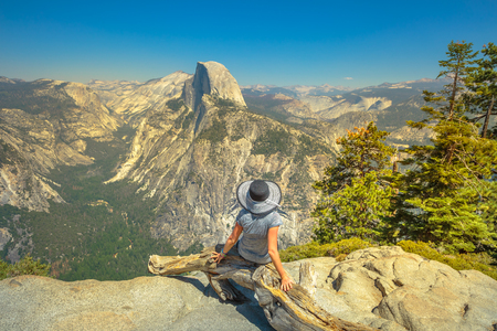 Young sitting woman contemplating Glacier Point in Yosemite National Park. Tired hiker relaxing down at popular Half Dome from Glacier Point overlook. Summer travel holidays concept. California, USA