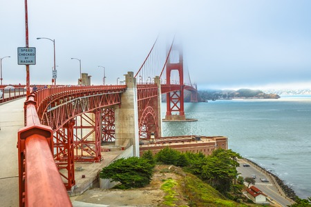 Fort Point view of Golden Gate Bridge south shore, symbol landmark of San Francisco, California, United States. Typical fog in summertime. Travel and holidays concept.