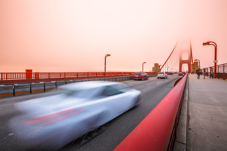 Cars crossing the San Francisco, Californian Golden Gate Bridge from the Presidio Pacific point to the north at sunset light. People along the bridge in the fog. Motion blur effect. Banco de Imagens