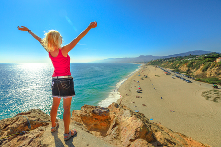 Caucasian female looking Point Dume State Beach from Point Dume promontory on Malibu coast in CA, United States. Carefree woman with open arms in California West Coast. Blue sky, sunny. Copy space.