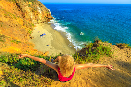 Carefree female from promontory looks Pirates Cove, a hidden sandy beach in a small cove on west side of Point Dume on Malibu coast in CA, United States. Caucasian woman in California West Coast.