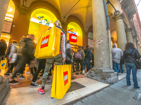 Bologna, Italy - December 6, 2018: woman with Lego shopping bags full of Lego bricks. At storefront of Lego store of Bologna in Italy, just inaugurated on 6th December 2018.