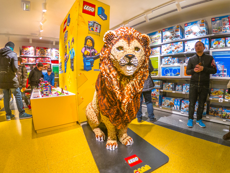 Bologna, Italy - December 6, 2018: toys store of Bologna, Lego bricks. In Via Indipendenza street of Bologna city downtown. King Lion big statue.