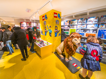 Bologna, Italy - December 6, 2018: little customers with King Lion big statue at toys store of Bologna, Lego bricks. In Via Indipendenza street of Bologna city downtown. Editorial