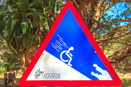 St Lucia, South Africa - Aug 30, 2014: African wildlife warning sign for ground slope because wheelchairs that can end up eaten by Nile Crocodiles. ISimangaliso Wetland Park, Ezemvelo kzn wildlife. Editorial
