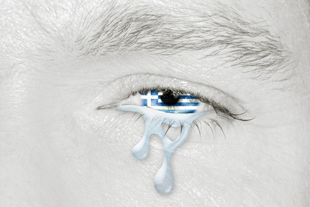 Crying eye with the flag of Greece in iris on black and white face. Concept of sadness for Greek pain about financial crisis, austerity, financial plan and patriotic metaphor. Stock Photo