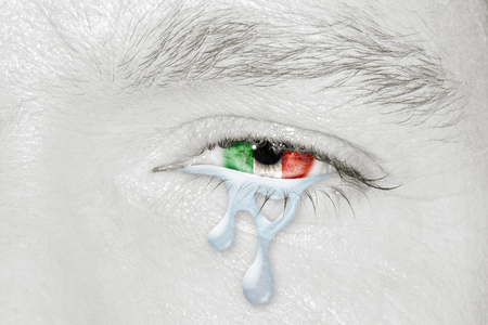 Crying eye with the flag of Italy in iris on black and white face. Concept of sadness for Italian pain about financial crisis, austerity, financial plan and patriotic metaphor.