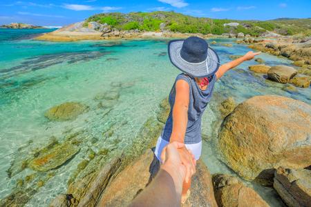 Australia summer holidays. Follow me POV. Woman in hat holding hand of her friend at William Bay National Park, Denmark region, Western Australia. Tropical destination of Madfish Beach.