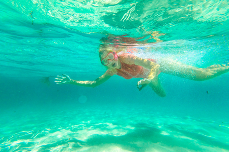 Young woman snorkeling in natural pool of Denmark Region, Western Australia. Female apnea with pink wetsuit. Watersport activity in Greens Pool, William Bay NP. Watersport activity in Australia.