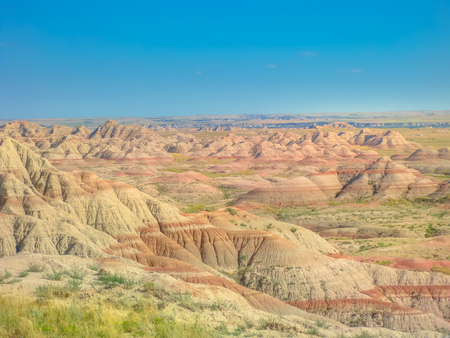 Surreal desert landscape of rugged pinnacles at Badlands National Park in South Dakota, United States. American travel destination. Aerial view. Blue sky in a sunny day. Copy space.