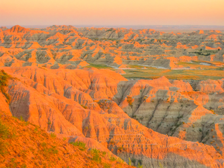 Colorful eroded pinnacles of Badlands National Park in South Dakota, United States at sunset light. American travel destination.