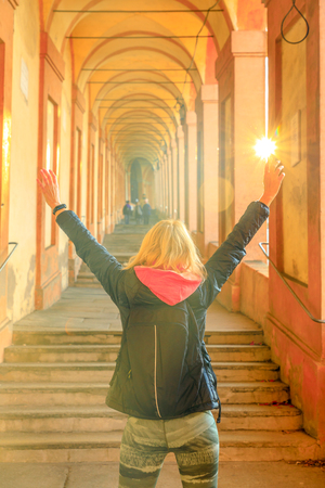 Happy woman with raised arms under San Lucas archway: the longest archway in the world leading to San Luca Sanctuary in Bologna, Italy. Vertical shot. Stockfoto