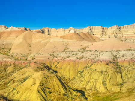 Yellow Mounds Overlook at Badlands National Park, South Dakota, United States. Upper layers were weathered into a yellow soil, called Yellow Mounds. Blue sky with copy space. Stock Photo