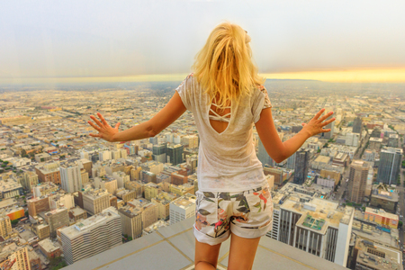 Aerial view of Los Angeles skyline in California, United States. Travel and tourism american concept. Blonde tourist woman looking at Downtown of LA cityscape from observation deck. Sunset shot.