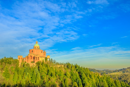 Scenic landscape of Sanctuary of Blessed Virgin of San Luca on Colle della Guardia in Bologna. Sunset light, blue sky. Historical church and pilgrimage destination in Emilia-Romagna, Italy. Copy space Фото со стока