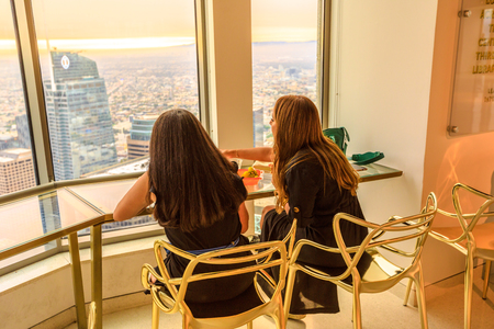Los Angeles, California, United States - August 9, 2018: lifestyle women enjoying the sunset skyline over Los Angeles Downtown from Oue Skyspace U.S. Bank Tower with observation deck on the 70th floor