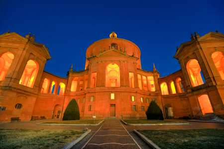Courtyard of Madonna di San Luca Sanctuary illuminated at night. Central facade of Basilica church of San Luca in Bologna, Emilia-Romagna, Italy. Famous landmark cityscape. Stock Photo