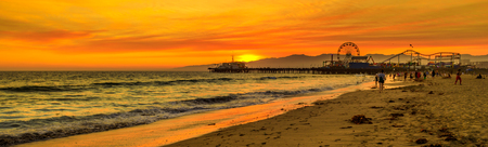 Scenic landscape of iconic Santa Monica Pier at orange sunset sky from the beach on Paficif Ocean. Santa Monica Historic Landmark, California, USA. Wide banner panorama.