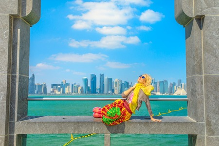 Happy blonde woman sitting under arches enjoying the view of Doha West Bay skyline outdoors of Museum of Islamic Art. Caucasian tourist in Qatar, Middle East, Arabian Peninsula. Sunny day blue sky.