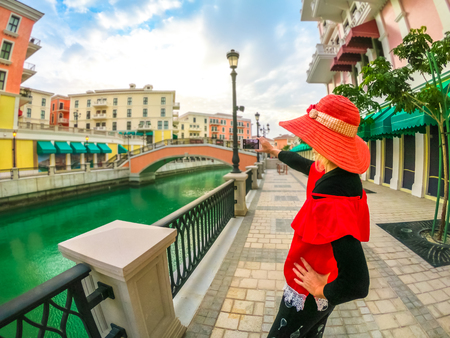 Woman in sunhat takes photo with smartphone of Venice, Venetian style waterfront village. Tourism in Middle East. Photographer takes pictures from Qanat Quartier in the Pearl-Qatar, Persian Gulf.