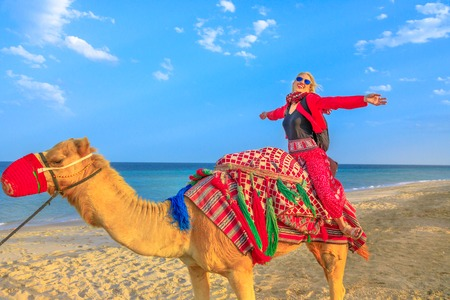 Inland sea is a major tourist destination for Qatar. Freedom woman riding camel on beach at Khor al Udaid in Persian Gulf. Caucasian blonde tourist enjoys camel ride in Middle East, Arabian Peninsula.