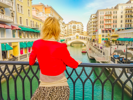 Back of blonde woman on balcony looks bridges and canals of Venice, a Venetian style waterfront village. Caucasian tourist at Qanat Quartier in the Pearl-Qatar, icon of Doha, Persian Gulf, Middle East Stockfoto