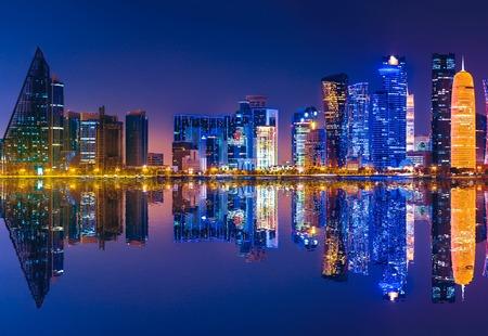 Éclairage d'horizon de Doha West Bay par nuit se reflétant dans la baie de Doha. Gratte-ciel modernes de Doha au Qatar, au Moyen-Orient, dans la péninsule arabique dans le golfe Persique. Scène urbaine de nuit.