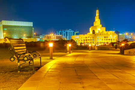 Bench and walkway in Souq Waqif Garden near Doha Corniche with Doha mosque on background. Doha center in Qatar, Middle East, Arabian Peninsula in Persian Gulf at night.