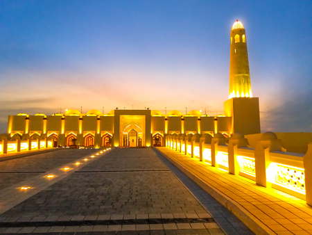 Lighted path towards State Grand Mosque illuminated at night in Doha Downtown, Middle East, Arabian Peninsula, Persian Gulf. Famous landmark in Doha West Bay. Stock Photo