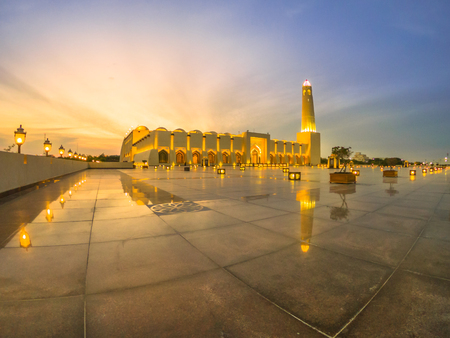 Wide angle view of State Grand Mosque with a minaret at twilight reflecting on marble pavement outdoors. Qatar State Mosque, Middle East, Arabian Peninsula in Persian Gulf. Famous touristic place.