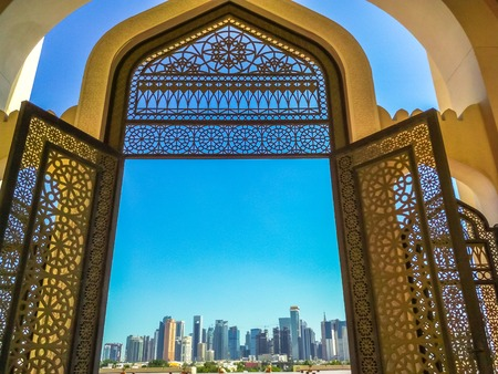 Modern skyscrapers of Doha West Bay skyline view from State Grand Mosque in Doha, Qatar, Middle East, Arabian Peninsula. Door of entrance at Mosque in Arabian style.