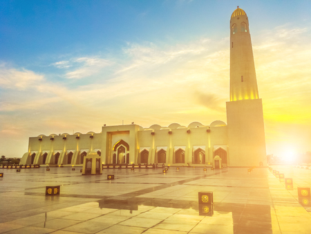 Scenic State Grand Mosque with a minaret at sunset light reflecting on marble pavement outdoors. Doha mosque in Downtown, Qatar, Middle East, Arabian Peninsula. Stock Photo
