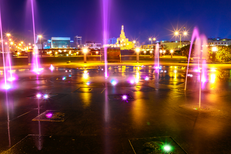 Colorful water fountain at Souq Waqif Park at Doha Corniche with Fanar Islamic Cultural Center and Minaret at night on background. Doha center in Qatar, Middle East, Arabian Peninsula in Persian Gulf.