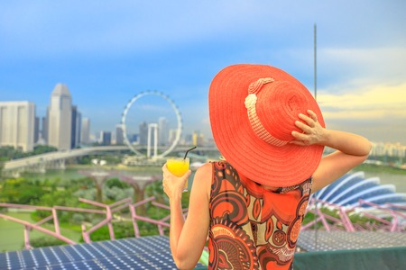 Lifestyle caucasian woman in wide hat drinking aperitif at rooftop cityscape skyline. Tourist enjoying above aerial view of Singapore marina. Travel holiday vacation in Singapore, Southeast Asia.