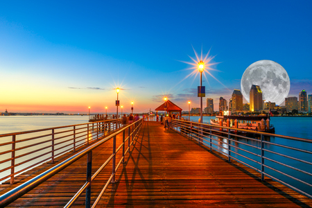 Scenic twiligtht view of Coronado wooden pier with docked ferry boat on Coronado Island, California, USA. San Diego skyline and urban downtown cityscape with big full moon over San Diego Bay. Banco de Imagens