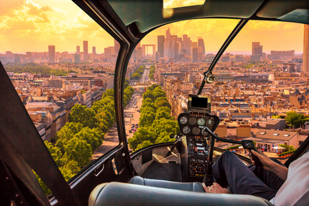 Helicopter cockpit flying on Charles de Gaulle square in Paris, French capital, Europe. Scenic flight above Paris skyline in France, Europe. Scenic urban cityscape and Parisian skyline on sunset.