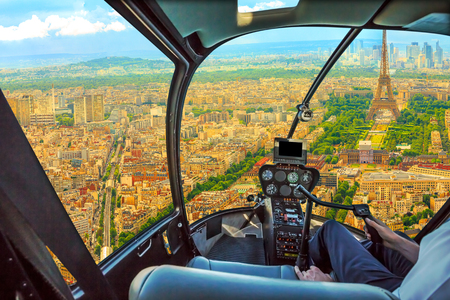 Helicopter cockpit aerial view of Tour Eiffel in Paris, French capital, Europe. Scenic flight above Paris skyline and cityscape, France.
