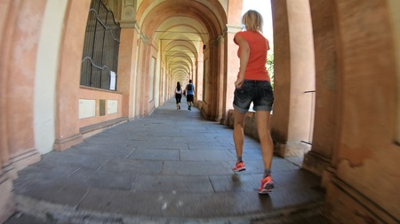 Bologna, Italy - September 29, 2018: people running under San Lucas portico: the longest porch in the world leading to the San Luca Sanctuary on Colle della Guardia. Bologna city of Italy. Фото со стока