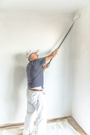 Senior man painting a white wall, with paint roller in empty room with copy space. Vertical Shot.