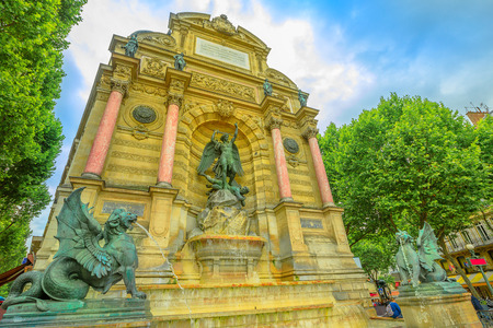 The Fontaine Saint-Michel is one of the most monumental fountains in the Place Saint-Michel. In front of the fountain, two water-spouting dragons. Perspective view. Paris, France in europe.