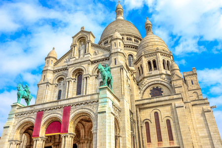 Bottom view of facade of Sacred Heart of Paris church in France. Basilique du Sacre-Coeur de Montmartre, the historic district of Paris Capital. Popular tourist landmark in a Capital of France.