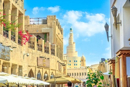 Doha, Qatar - February 20, 2019: details of Fanar Islamic Cultural Center with Spiral Mosque from main street in Souq Waqif old traditional market with cafes and restaurants. Sunny day with blue sky.