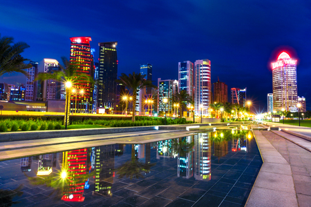 Doha West Bay high rises at night reflecting in the water of downtown park. Lighting skyscrapers of Doha skyline in Qatar, Middle East, Arabian Peninsula in Persian Gulf. Night urban scene. Reklamní fotografie